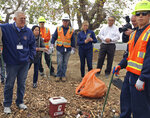 U.S. District Judge David Carter, left, speaks with workers cleaning up syringes mixed in with trash along the riverbed trail during a tour of a homeless encampment along the Santa Ana River in Anaheim, Calif., Wednesday, Feb. 14, 2018. Carter demanded that Orange County officials provide answers about what federal funding is available to feed and temporarily house people if they are moved. (AP Photo/Amy Taxin)