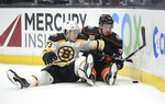 Boston Bruins defenseman Charlie McAvoy, left, and Anaheim Ducks center Derek Grant fall while competing for the puck during the second period of an NHL hockey game Friday, Feb. 15, 2019, in Anaheim, Calif. (AP Photo/Mark J. Terrill)
