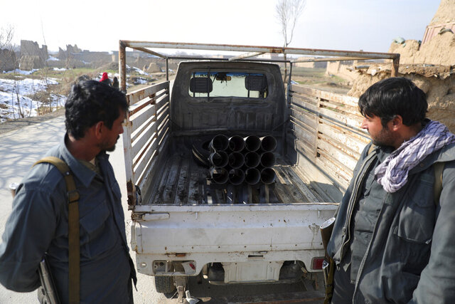 Afghan security personnel stand near a vehicle in which rockets were placed, in Bagram, north of Kabul, Afghanistan, Saturday, Dec. 19, 2020. Five rockets were fired at a major U.S. base in Afghanistan on Saturday, but there were no casualties, NATO and provincial officials said. (AP Photo/Rahmat Gul)