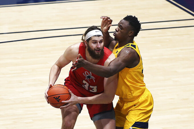 Richmond forward Grant Golden (33) is defended by West Virginia forward Oscar Tshiebwe (34) during the first half of an NCAA college basketball game Sunday, Dec. 13, 2020, in Morgantown, W.Va. (AP Photo/Kathleen Batten)