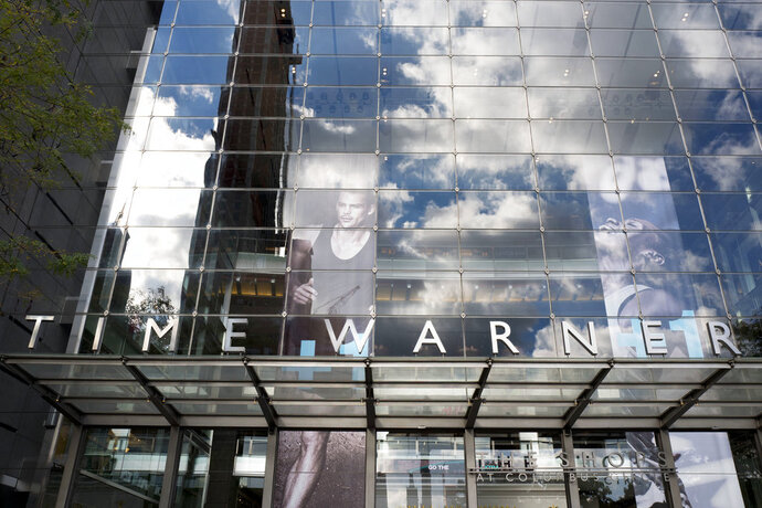 FILE - In this Oct. 24, 2016, file photo, clouds are reflected in the glass facade of the Time Warner building in New York. The judge presiding over the government's legal effort to block AT&T's purchase of Time Warner will likely deliver his verdict on Tuesday, June 12, 2018. (AP Photo/Mark Lennihan, File)