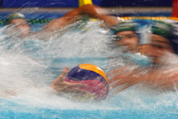 Players race for the ball at the start of a preliminary round men's water polo match between Hungary and Japan at the 2020 Summer Olympics, Tuesday, July 27, 2021, in Tokyo, Japan. (AP Photo/Mark Humphrey)