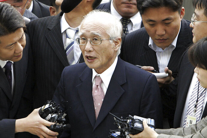 FILE - In this June 14, 2005 file photo, Kim Woo-choong, center, former chairman of collapsed conglomerate Daewoo Group, answers reporters' questions as he arrived at the Supreme Prosecutor's Office in Seoul, South Korea. Kim, the founder of now-collapsed business group whose rise and fall symbolized South Korea's much turbulent rapid economic growth in the 1970s, has died. He was 83.(AP Photo/ Lee Jin-man, File)