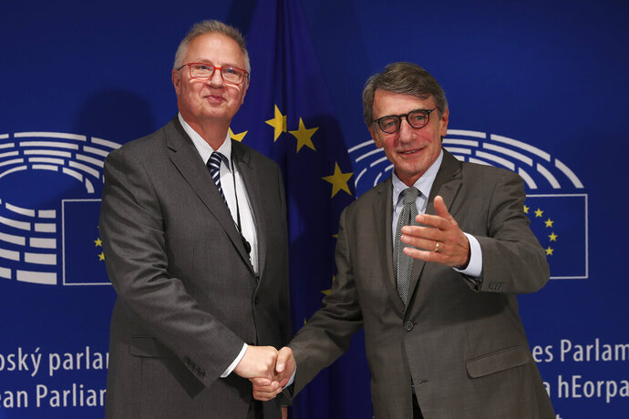 European Commissioner nominated for Neighbourhood and Enlargement Laszlo Trocssnyi, left, is welcomed by European Parliament President David Sassoli before their meeting at the European Parliament in Brussels, Tuesday, Sept. 24, 2019. (AP Photo/Francisco Seco)