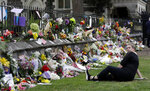 A woman reacts as she sits near the wall with floral tributes at the Botanical Gardens, Saturday, March 16, 2019, Christchurch, New Zealand. (AP Photo/Mark Baker)