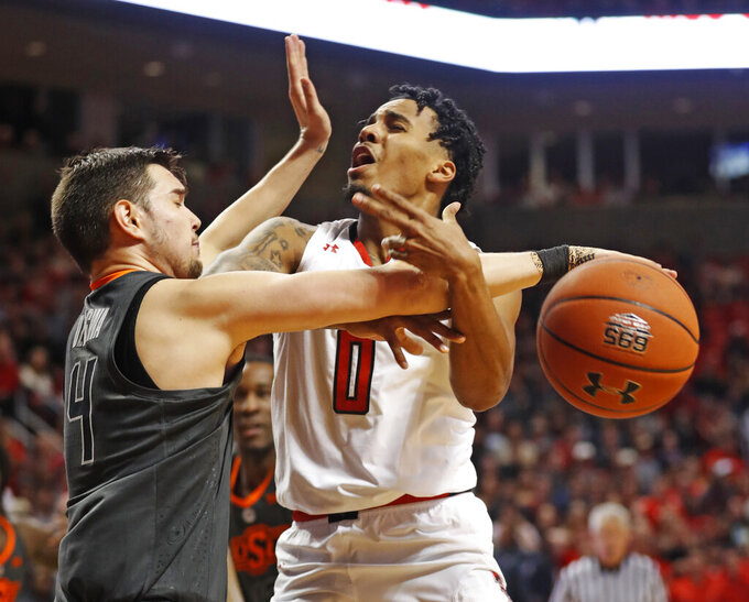 Oklahoma State's Thomas Dziagwa (4) fouls Texas Tech's Kyler Edwards (0) as he shoots the ball during the second half of an NCAA college basketball game Wednesday, Feb. 27, 2019, in Lubbock, Texas. (AP Photo/Brad Tollefson)