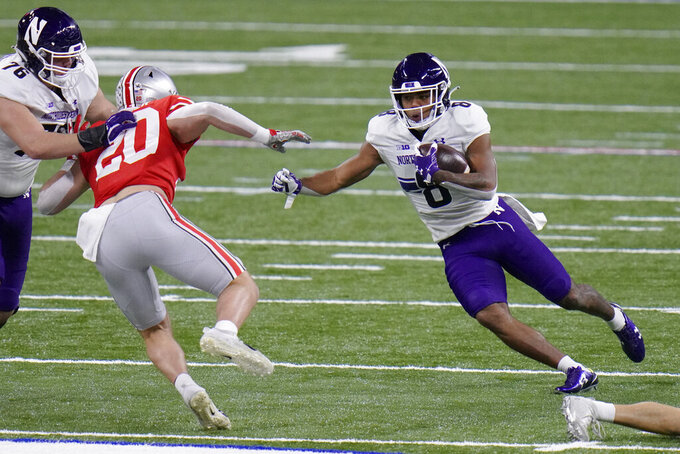 Northwestern wide receiver Kyric McGowan (8) runs with the ball as Ohio State linebacker Pete Werner (20) defends during the first half of the Big Ten championship NCAA college football game, Saturday, Dec. 19, 2020, in Indianapolis. (AP Photo/AJ Mast)