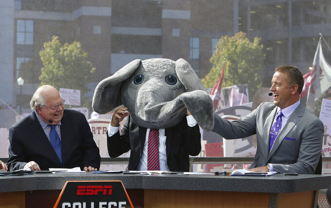 "FILE - In this Oct. 22, 2016, file photo, ESPN's Lee Corso wears Big Al's mascot head after picking Alabama to win over Texas A&M as Vern Lundquist, left, and Kirk Herbstreit laugh on the set of ESPN's College GameDay outside Bryant-Denny Stadium in Tuscaloosa, Ala. The Par 3 Contest is out at the spectator-free Masters in November. ESPN's ""College GameDay"" is in. Augusta National announced Tuesday, Oct. 27, 2020, more changes to a Masters tournament that will be unlike any of the previous 83. The most unusual of all is ESPN's popular college football pregame show taking place on a stage that overlooks Ike's Pond and the ninth green of the Par 3 course. (Erin Nelson/The Tuscaloosa News via AP, File)"
