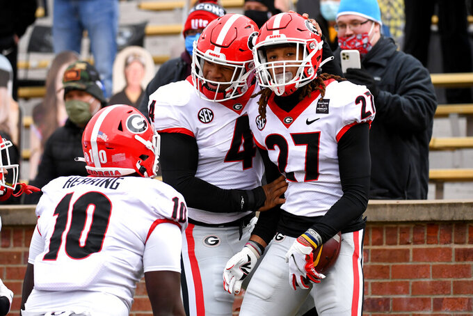 Georgia defensive back Eric Stokes (27) is congratulated by teammates Nolan Smith (4) and Malik Herring after intercepting a pass during the first half of an NCAA college football game against Missouri Saturday, Dec. 12, 2020, in Columbia, Mo. (AP Photo/L.G. Patterson)