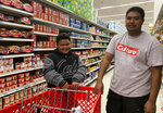 Tyrone Quinata, 23, and his nephew Rayden Gofigan, 11, shop for batteries and other necessities in Tamuning, Guam on Thursday, Feb. 21, 2019.  An intensifying tropical storm in the Pacific is bearing down on Micronesia and could threaten the U.S. territory of Guam in the coming days.  (AP Photo/Grace Garces Bordallo)