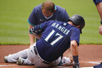 A trainer looks at Seattle Mariners' Mitch Haniger after Haniger was hit by a pitch in the first inning of a baseball game against the Cleveland Indians, Sunday, June 13, 2021, in Cleveland. Haniger left the game after the incident. (AP Photo/Tony Dejak)