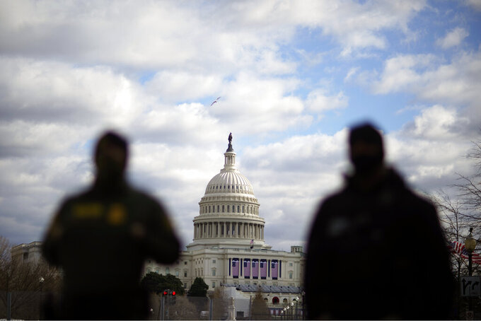 Law enforcement stand near the Capitol ahead of the inauguration of President-elect Joe Biden and Vice President-elect Kamala Harris, Sunday, Jan. 17, 2021, in Washington. (AP Photo/David Goldman)