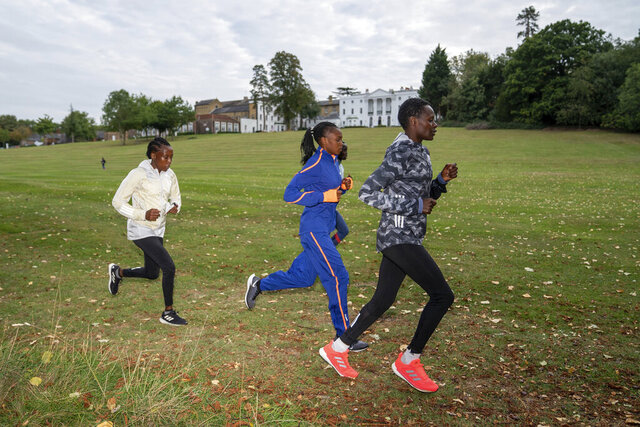 In this image issued by London Marathon Events, Kenya's Edith Chelimo, right, trains in the grounds of the official hotel and biosecure bubble in London, Monday Sept. 28, 2020, ahead of the elite-only 2020 London Marathon on Sunday Oct. 4. The 40th Race will take place on a closed-loop circuit around St James's Park in central London. (Bob Martin/London Marathon Events via AP)