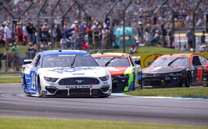 Chase Briscoe (14) leads the pack of cars through Turn 2 during a NASCAR Cup Series auto race at Indianapolis Motor Speedway, Sunday, Aug. 15, 2021, in Indianapolis. (AP Photo/Doug McSchooler)