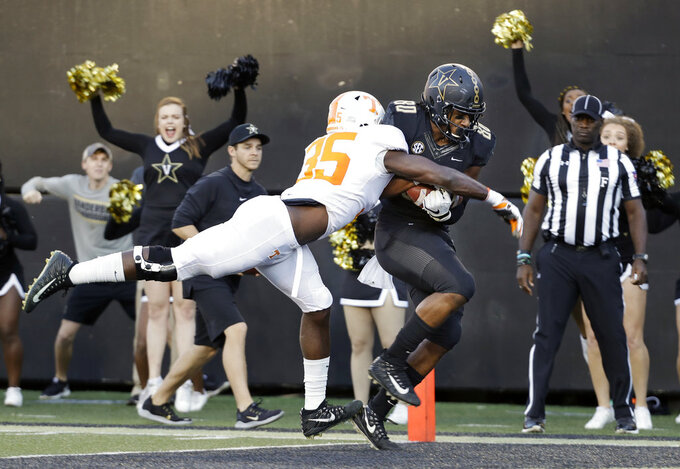 Vanderbilt tight end Jared Pinkney (80) scores a touchdown on a 17-yard pass as he is defended by Tennessee linebacker Daniel Bituli (35) in the first half of an NCAA college football game Saturday, Nov. 24, 2018, in Nashville, Tenn. (AP Photo/Mark Humphrey)