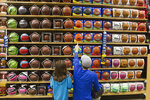 FILE - In this April 1, 2016, file photo, Rod Call and his daughter Savannah Call, 5, pick out basketballs while shopping on in Traverse City, Mich. Companies that make merchandise for the National Basketball Association players are in the crosshairs of President Donald Trump's escalating China trade wars. The stakes are high as U.S. sales from sports licensed merchandise including NBA items rang up $21 billion last year, according to  Licensing International, a trade group.  Sales on NBAStore.com rose 15% during the 12-month period through August, according to the NBA League. And many of the sports brands ranging from Adidas to Puma rely on China for at least some of their sourcing.(Jan-Michael Stump/Traverse City Record-Eagle via AP, File)