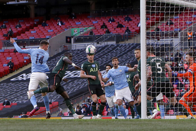 Manchester City's Aymeric Laporte, left, scores the opening goal during the English League Cup final soccer match between Manchester City and Tottenham Hotspur at Wembley stadium in London, Sunday, April 25, 2021. (AP Photo/Alastair Grant)