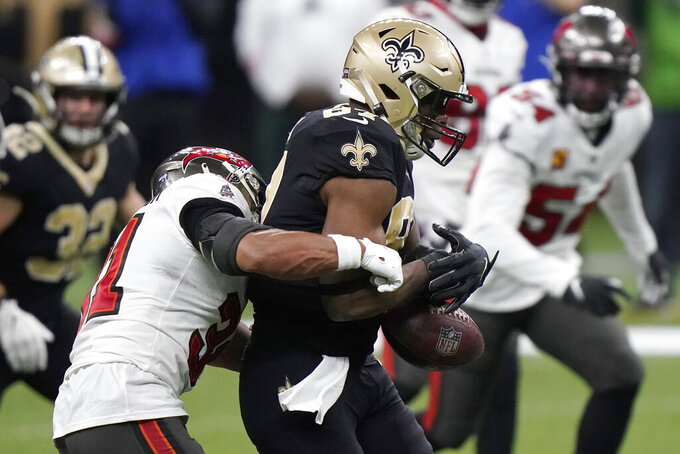 New Orleans Saints tight end Jared Cook, center, fumbles the ball as he is hit by Tampa Bay Buccaneers strong safety Antoine Winfield Jr. during the second half of an NFL divisional round playoff football game, Sunday, Jan. 17, 2021, in New Orleans. The Buccaneers' Devin White recovered the ball. (AP Photo/Brynn Anderson)