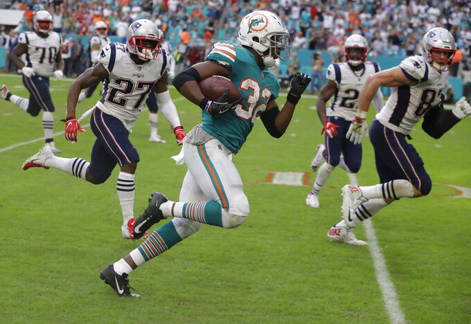 "FILE - In this Dec. 9, 2018, file photo, Miami Dolphins running back Kenyan Drake (32) runs for a touchdown during the second half of an NFL football game against the New England Patriots, in Miami Gardens, Fla. The NFL revealed 70 of the 100 greatest plays in league history on Friday night with a TV special produced by NFL Films that has everything from spectacular offensive performances to defensive gems. In balloting conducted by The Associated Press, 68 media members on a nationwide panel voted for their top 100. Among those disclosed is the play some have dubbed ""The Drake Escape."" (AP Photo/Lynne Sladky, File)"