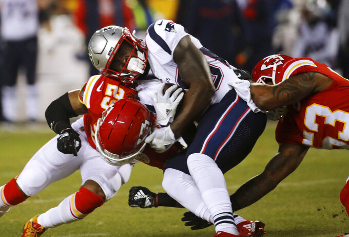 New England Patriots running back Sony Michel (26) is tackled by Kansas City Chiefs defensive back Eric Berry (29) and inside linebacker Anthony Hitchens (53) during the first half of the AFC Championship NFL football game, Sunday, Jan. 20, 2019, in Kansas City, Mo. (AP Photo/Charlie Riedel)