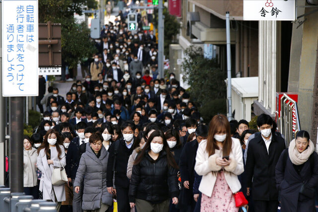 People wear masks as they commute during the morning rush hour Thursday, Feb. 20, 2020, in Chuo district in Tokyo. A test event for the Tokyo Olympics scheduled for later this month that would have involved some non-Japanese athletes is being rejiggered because of fear of the spreading virus from China. It will now involve only Japanese athletes. (AP Photo/Kiichiro Sato)