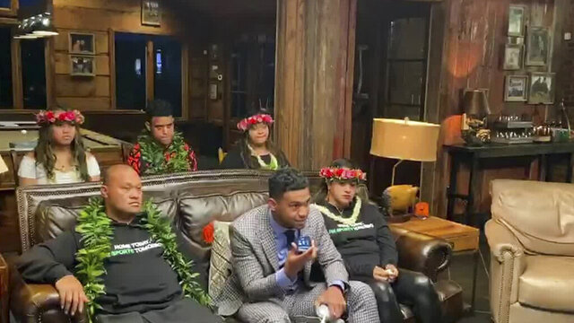 In this still image from video provided by the NFL, Tua Tagovailoa, front center, holds up a phone during the NFL football draft Thursday, April 23, 2020. The Miami Dolphins selected Tagovailoa with the fifth pick. (NFL via AP)