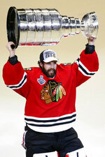 "FILE - In this June 10, 2015, file photo, Chicago Blackhawks' goalie Corey Crawford hoists the Stanley Cup trophy after defeating the Tampa Bay Lightning in Game 6 of the NHL hockey Stanley Cup Final series, in Chicago. The Blackhawks will not re-sign goaltender Corey Crawford in free agency, potentially signaling a more extensive rebuild for one of the NHL's marquee franchises. General manager Stan Bowman said he had a ""bit of an emotional"" conversation with Crawford on Thursday, Oct. 8, 2020. (AP Photo/Charles Rex Arbogast, File)"