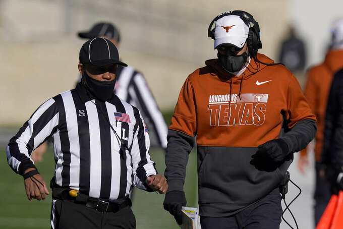 Texas head coach Tom Herman, right, talks with line judge Darren Deckard, left, during the first half of an NCAA college football game against Kansas State in Manhattan, Kan., Saturday, Dec. 5, 2020. (AP Photo/Orlin Wagner)