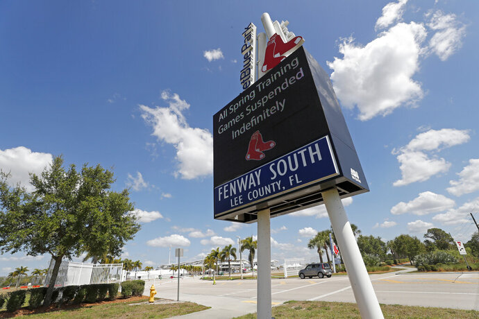 A sign announcing the suspension of spring training baseball games is displayed outside a closed JetBlue Park, the spring training home of the Boston Red Sox, Friday, March 13, 2020, in Fort Myers, Fla. Major League Baseball has suspended the rest of its spring training game schedule because of the coronavirus outbreak. The league is also delaying the start of its regular season by at least two weeks. (AP Photo/Elise Amendola)