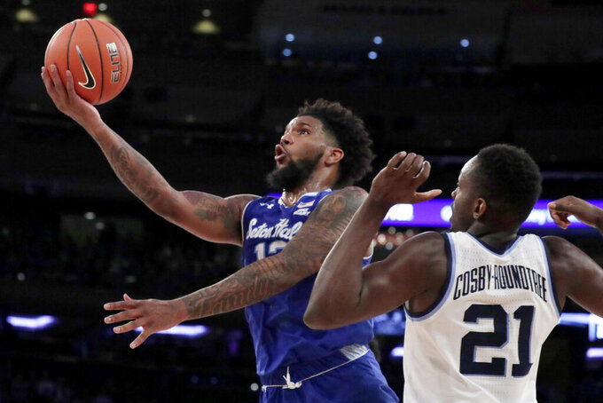 FILE- In this March 16, 2019, file photo, Seton Hall guard Myles Powell, left, goes up for a shot against Villanova forward Dhamir Cosby-Roundtree during the second half of an NCAA college basketball game in the championship of the Big East Conference tournament in New York. With preseason All America Myles Powell and three other starters back, it's no surprise Seton Hall is No. 12.(AP Photo/Julio Cortez, File)