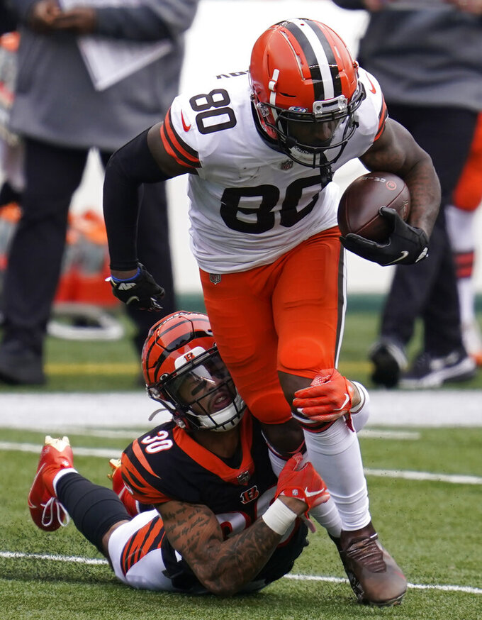 Cleveland Browns' Jarvis Landry (80) is tackled by Cincinnati Bengals' Jessie Bates (30) during the first half of an NFL football game Sunday, Oct. 25, 2020, in Cincinnati. (AP Photo/Michael Conroy)