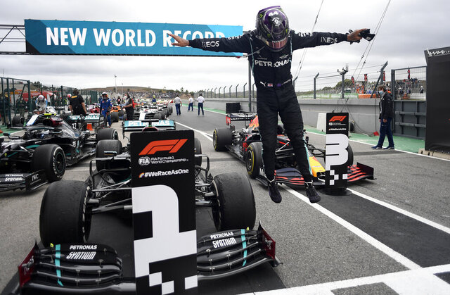 Mercedes driver Lewis Hamilton of Britain jumps out of his car after his record breaking 92nd win at the Formula One Portuguese Grand Prix at the Algarve International Circuit in Portimao, Portugal, Sunday, Oct. 25, 2020. (Jorge Guerrero, Pool via AP)
