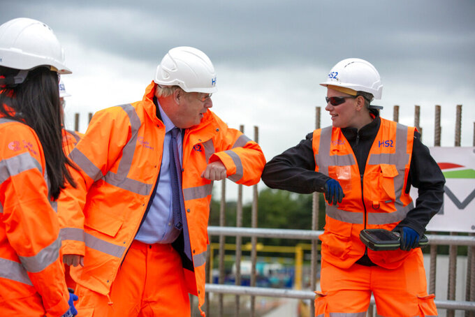 """Britain's Prime Minister Boris Johnson, center left, greets a worker during a visit to the HS2 Solihull Interchange building site in Solihull, England, Friday, Sept. 4, 2020. Construction is set to formally begin on Britain's 106 billion-pound ($140 billion) high-speed railway project, aiming to forge better connections between cities for decades to come. Transport Secretary Grant Shapps defended the project, which has its """"shovels in the ground"""" moment just as the country is wondering whether the over-budget and often-delayed project offers good value at a time when the the COVID-19 pandemic has enshrined the idea of working from home. (Andrew Fox/Pool Photo via AP)"""