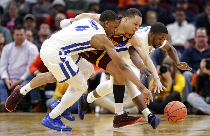 Buffalo's Davonta Jordan, left, Central Michigan's Larry Austin Jr., center, and Buffalo's Dontay Caruthers reach for the ball during the second half of an NCAA college basketball game in the semifinals of the Mid-American Conference men's tournament Friday, March 15, 2019, in Cleveland. Buffalo won 85-81. (AP Photo/Tony Dejak)