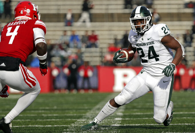 Michigan State running back Elijah Collins (24) rushes past Rutgers defensive back Tim Barrow (4) during the first half of an NCAA college football game Saturday, Nov. 23, 2019, in Piscataway, N.J. (AP Photo/Adam Hunger)