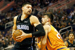 Orlando Magic's Nikola Vucevic, left, looks to the basket past Phoenix Suns' Dario Saric (20) during the first half of an NBA basketball game Friday, Jan. 10, 2020, in Phoenix. (AP Photo/Darryl Webb)