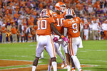 Clemson's Trevor Lawrence, back, and Joseph Ngata, left, celebrate a touchdown by Travis Etienne, right, during the first half of an NCAA college football game against Boston College, Saturday, Oct. 26, 2019, in Clemson, S.C. (AP Photo/Richard Shiro)