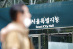 A man wearing a face mask walks near Seoul City Hall in Seoul, South Korea, Wednesday, July 15, 2020. The city government of the South Korean capital, Seoul, said Wednesday it will launch an investigation into allegations of sexual misconduct surrounding late Mayor Park Won-soon, who was found dead after one of his secretaries filed a complaint claiming yearslong abuse. (AP Photo/Lee Jin-man)