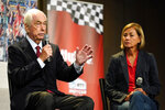 Roger Penske speaks as Iowa Gov. Kim Reynolds, right, looks on during a news conference at Hy-Vee Corp. headquarters, Thursday, Aug. 19, 2021, in West Des Moines, Iowa. IndyCar will return next season to Iowa Speedway, a short oval track beloved by fans and drivers that had fallen off the schedule after 14 years. The track located in Newton will host a doubleheader next July in a deal brokered between IndyCar Series owner Roger Penske, team owner Bobby Rahal and grocery chain Hy-Vee. (AP Photo/Charlie Neibergall)