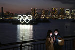 In this March 12, 2020, file photo, two women take a selfie with the Olympic rings in the background in the Odaiba section of Tokyo. The CEO of the Tokyo Olympics and the IOC member in charge of Japan's games have both dismissed a new study from the University of Oxford that finds Tokyo is the most expensive Summer Games dating back to 1960. (AP Photo/Jae C. Hong, File)
