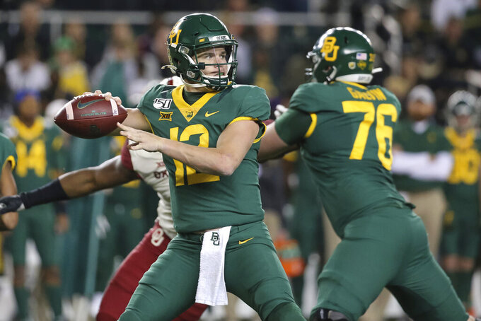 FILE - In this Nov. 16, 2019, file photo, Baylor quarterback Charlie Brewer (12) looks for a receiver during the first half of the team's NCAA college football game against Oklahoma in Waco, Texas. Baylor and Houston play this week for the first time since 1995, when both teams were in the Southwest Conference. Brewer enters his senior season with 7,742 yards passing, third in school history behind 2011 Heisman Trophy winner Robert Griffin III (10,366) and Bryce Petty (8,195). (AP Photo/Ray Carlin, File)