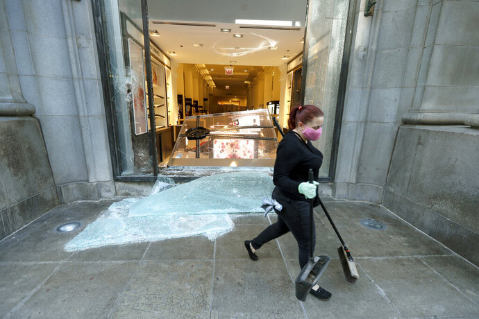 A volunteer worker walks past a shattered display window early Sunday morning, May 31, 2020, at the downtown Macy's store in Chicago, after a night of unrest and protests over the death of George Floyd, a black man who was in police custody in Minneapolis. Floyd died after being restrained by Minneapolis police officers on Memorial Day. (AP Photo/Charles Rex Arbogast)