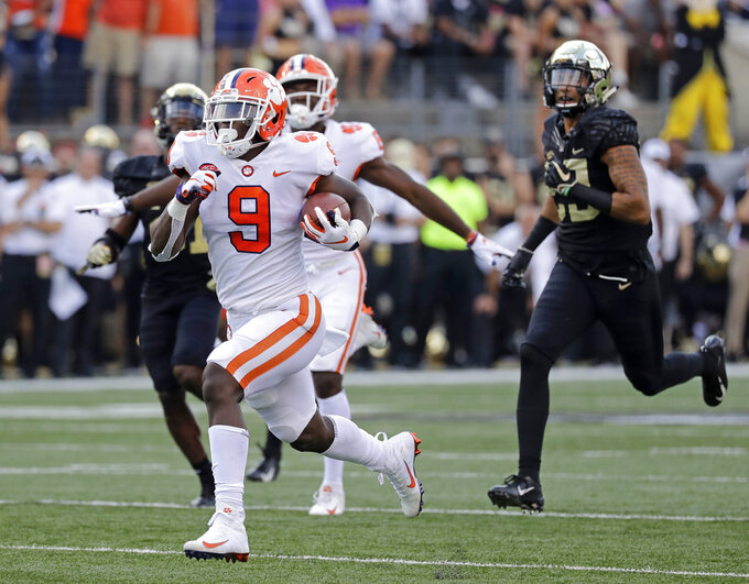 Clemson's Travis Etienne (9) runs past Wake Forest players for a touchdown during the first half of an NCAA college football game in Charlotte, N.C., Saturday, Oct. 6, 2018. (AP Photo/Chuck Burton)