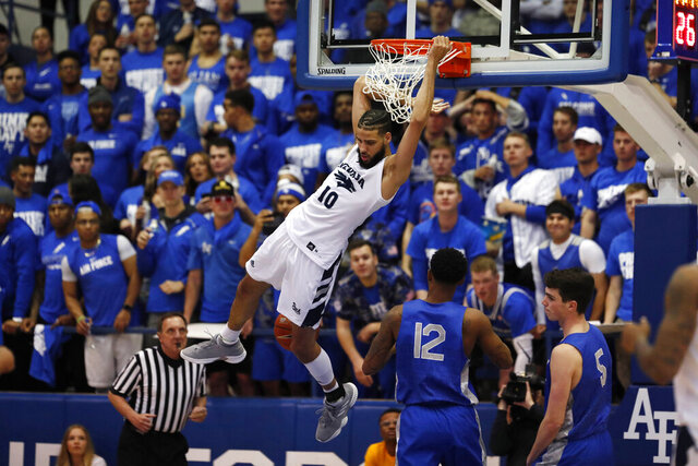 FILE--In this Tuesday, March 5, 2019, file photograph, Nevada forward Caleb Martin hangs on the rim after dunking the ball for a basket against Air Force in the second half of an NCAA college basketball game at Air Force Academy, Colo. Following the lead of California and joining an increasing number of other states, Colorado lawmakers are considering a bill on Thursday, Feb. 6, 2020, to allow college student athletes to profit from their name and image. (AP Photo/David Zalubowski)