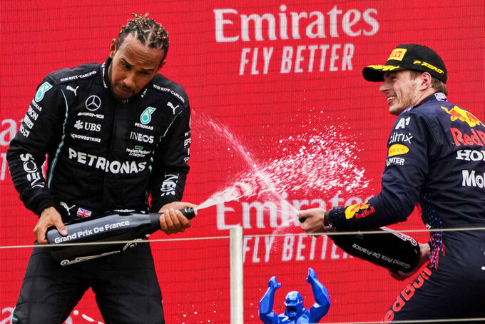 Red Bull driver Max Verstappen of the Netherlands, right, celebrates from the podium after winning with second place Mercedes driver Lewis Hamilton of Britain from the podium during the French Formula One Grand Prix at the Paul Ricard racetrack in Le Castellet, southern France, Sunday, June 20, 2021. (AP Photo/Francois Mori)