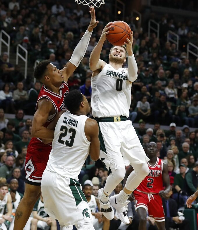Michigan State forward Kyle Ahrens (0) grabs a rebound next to Northern Illinois forward Lacey James during the second half of an NCAA college basketball game, Saturday, Dec. 29, 2018, in East Lansing, Mich. (AP Photo/Carlos Osorio)