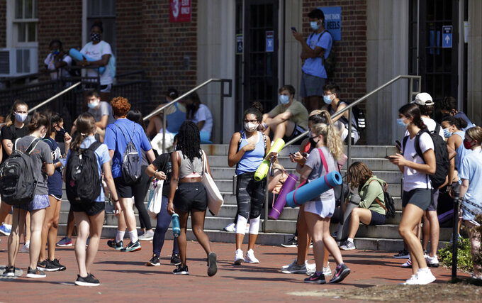 University of North Carolina students wait outside of Woolen Gym on the Chapel Hill, N.C., campus as they wait to enter for a fitness class Monday, Aug. 17, 2020. The University announced minutes before that all classes will be moved online starting Wednesday, Aug. 19 due to COVID clusters on campus. (Julia Wall/The News & Observer via AP)