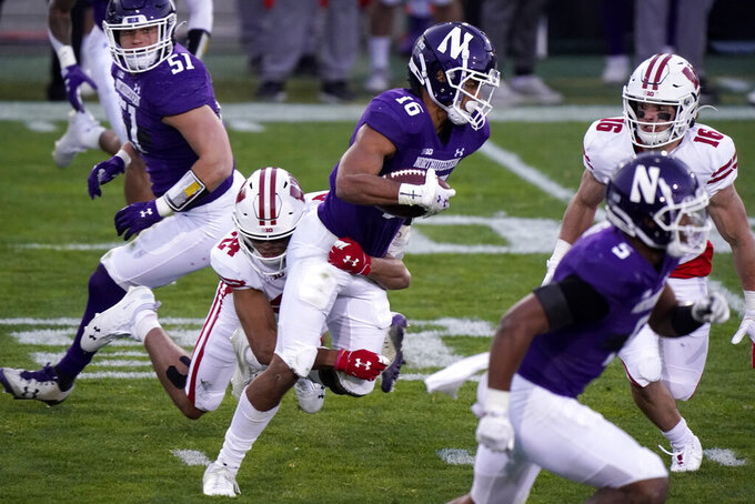 Northwestern defensive back Brandon Joseph (16) is tackled by Wisconsin wide receiver Adam Krumholz after intercepting a pass during the first half of an NCAA college football game in Evanston, Ill., Saturday, Nov. 21, 2020. (AP Photo/Nam Y. Huh)