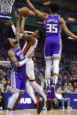 Miami Heat center Hassan Whiteside, center, goes to the basket between Sacramento Kings' Harry Giles III, left, and Marvin Bagley III, right, during the first quarter of an NBA basketball game Friday, Feb. 8, 2019, in Sacramento, Calif. (AP Photo/Rich Pedroncelli)