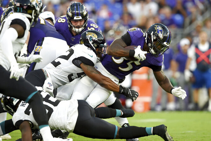 Baltimore Ravens running back Gus Edwards (35) is tackled by Jacksonville Jaguars defensive end Lyndon Johnson during the first half of an NFL football preseason game Thursday, Aug. 8, 2019, in Baltimore. (AP Photo/Gail Burton)